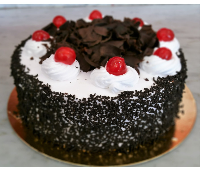 The Black Forest Cake is made up of a chocolate layer cake with cherries in the middle and whipped cream on top and  decorated with chocolate curls